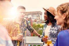 Groupe millenial multi-ethnique d'amis faisant la fête et appréciant une bière sur le terrasse de dessus de toit au coucher du so Photos stock