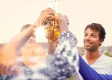 Groupe millenial multi-ethnique d'amis faisant la fête et appréciant une bière sur le terrasse de dessus de toit au coucher du so Image libre de droits