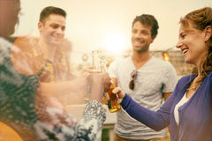 Groupe millenial multi-ethnique d'amis faisant la fête et appréciant une bière sur le terrasse de dessus de toit au coucher du so Images stock