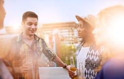 Groupe millenial multi-ethnique d'amis faisant la fête et appréciant une bière sur le terrasse de dessus de toit au coucher du so Photographie stock