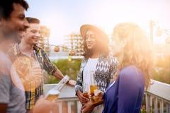Groupe millenial multi-ethnique d'amis faisant la fête et appréciant une bière sur le terrasse de dessus de toit au coucher du so Photo libre de droits