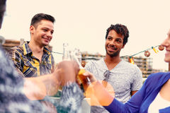 Groupe millenial multi-ethnique d'amis faisant la fête et appréciant une bière sur le terrasse de dessus de toit au coucher du so Photographie stock libre de droits