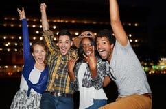 Groupe millenial multi-ethnique d'amis posant pour une photo utilisant l'éclair dehors à la nuit Image stock