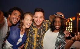 Groupe millenial multi-ethnique d'amis prenant la photo de selfie par le téléphone portable sur le terrasse de dessus de toit ave Photo libre de droits