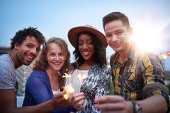 Groupe millenial multi-ethnique de cierges magiques friendsfolding sur le terrasse de dessus de toit au coucher du soleil Photo libre de droits