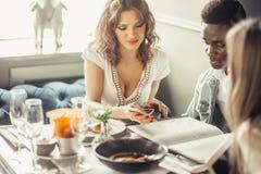 Groupe mixte de jeunes étudiants prenant le déjeuner ensemble en café Image libre de droits