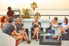 Groupe multi-ethnique attirant d'amis ayant une vie sociale à un barbecue de dessus de toit Photos libres de droits