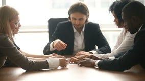 Groupe multi-ethnique d'affaires assemblant le puzzle denteux ensemble à la table de conférence banque de vidéos