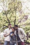 Groupe multi-ethnique d'amis ayant l'amusement dans le parc près d'Eiffel Images stock