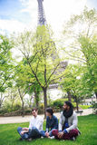 Groupe multi-ethnique d'amis ayant l'amusement dans le parc près d'Eiffel Images libres de droits