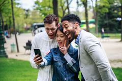 Groupe multi-ethnique d'amis ayant l'amusement dans le parc près d'Eiffel Image libre de droits