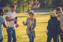 Groupe multi-ethnique d'amis ayant l'amusement dans un parc Photographie stock