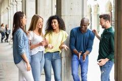 Groupe multi-ethnique d'amis ayant l'amusement ensemble dans le backg urbain Images libres de droits