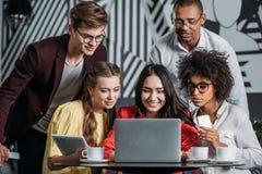 groupe multi-ethnique d'amis heureux regardant l'ordinateur portable Photos libres de droits