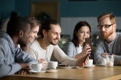 Groupe multi-ethnique d'amis parlant et à l'aide des smartphones à m Image libre de droits