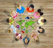 Groupe multi-ethnique d'enfants avec la carte du monde Photographie stock libre de droits
