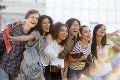 Groupe multi-ethnique de jeunes étudiants heureux se tenant dehors Images stock