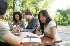 Groupe multi-ethnique de jeunes étudiants s'asseyant et étudiant Images libres de droits