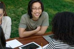 Groupe multi-ethnique de jeunes étudiants s'asseyant et étudiant Photos stock