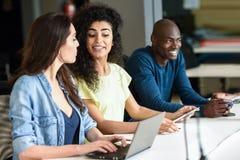 Groupe multi-ethnique des jeunes étudiant avec l'ordinateur portable Image stock