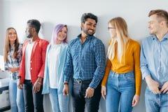 Groupe multi-ethnique des jeunes dans la tenue de détente d'isolement au-dessus du fond gris Image stock