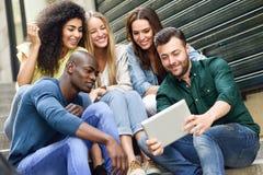 Groupe multi-ethnique des jeunes regardant une tablette Photographie stock libre de droits