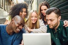 Groupe multi-ethnique des jeunes regardant une tablette Photographie stock