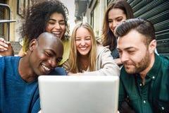 Groupe multi-ethnique des jeunes regardant une tablette Image stock