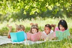 Groupe multiculturel apprenant à lire des enfants Image stock