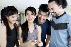 Groupe multiracial avec le téléphone portable au gymnase Photographie stock