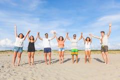Groupe multiracial d'amis avec les mains augmentées sur la plage Photographie stock libre de droits