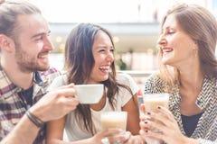 Groupe multiracial d'amis ayant un café ensemble Images libres de droits