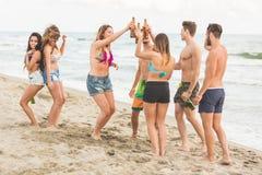 Groupe multiracial d'amis ayant une partie sur la plage Photo stock
