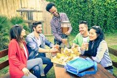 Groupe multiracial d'amis heureux mangeant et grillant au BBQ Photographie stock