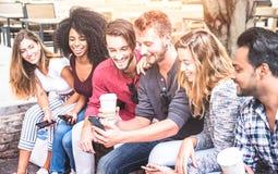 Groupe multiracial d'amis utilisant le téléphone intelligent mobile au centre d'enseignement supérieur photo libre de droits