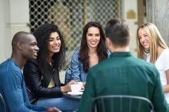 Groupe multiracial de cinq amis ayant un café ensemble Photos stock
