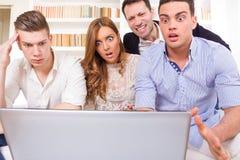Groupe occasionnel frustrant d'amis s'asseyant sur le divan regardant l Photographie stock libre de droits