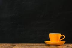 Groupe orange isolé de tasse de thé placé sur le noir Image stock