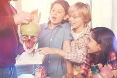 Groupe positif d'élèves visitant la classe avec plaisir image stock