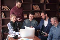 Groupe r?ussi de concepteurs discutant un nouveau projet de publicit? image stock