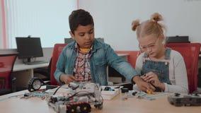 Groupe racial mixte d'enfants d'école se reposant à la classe avec le robot diy, concept d'éducation de tige clips vidéos