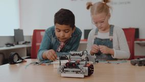 Groupe racial mixte d'enfants d'école se reposant à la classe avec le robot diy, concept d'éducation de tige banque de vidéos