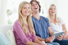 Groupe riant d'amis s'asseyant comme ils utilisent un comprimé Photographie stock