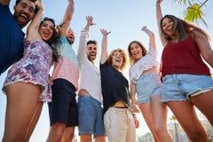 Groupe riant d'amis soulevant des mains riant ensemble Image stock