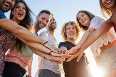 Groupe riant d'amis tenant des mains ensemble dehors Photos libres de droits