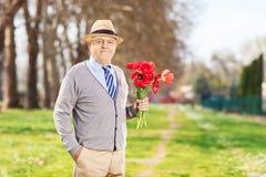 Groupe se tenant masculin supérieur de tulipes rouges en parc Images stock