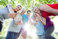 Groupe sportif heureux avec des pouces  Image stock
