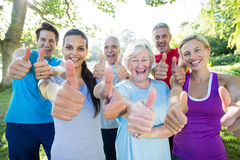 Groupe sportif heureux avec des pouces  Photo stock
