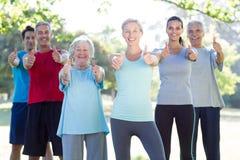 Groupe sportif heureux souriant à l'appareil-photo avec des pouces  Photographie stock libre de droits