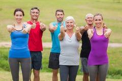 Groupe sportif heureux souriant à l'appareil-photo avec des pouces  Photo stock